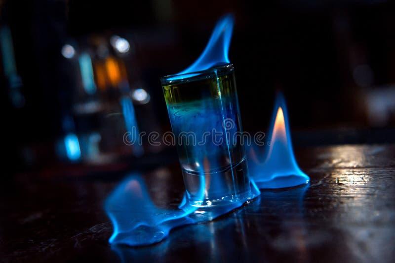 Brennendes Schusscocktail in der Bar mit Restlichtern lizenzfreies stockbild