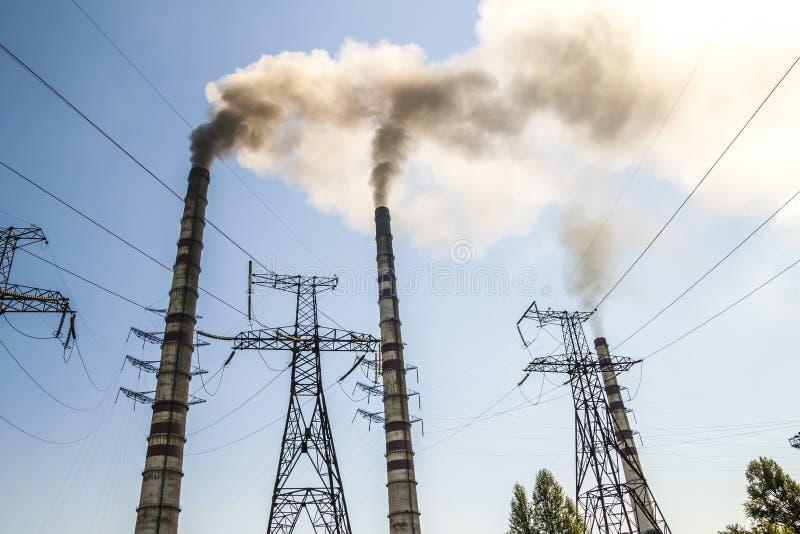 Brennendes Wirtschaftsmachtkraftwerk der Kohle mit Schornsteinen Schmutziges smo stockfoto