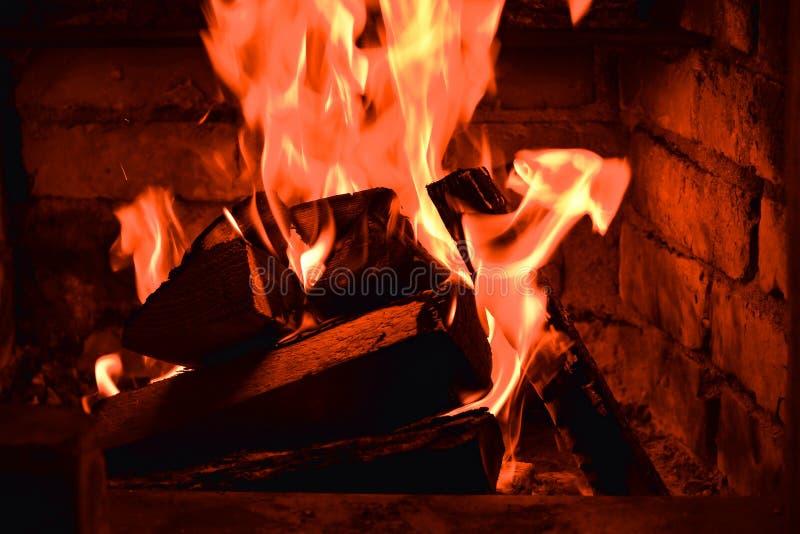 Brennholz, das in den Feuerbränden im Kamin brennt Der Ziegelsteinofen gibt Hitze und Hitze von den gebrannten Klotz Brennende Ko stockbild