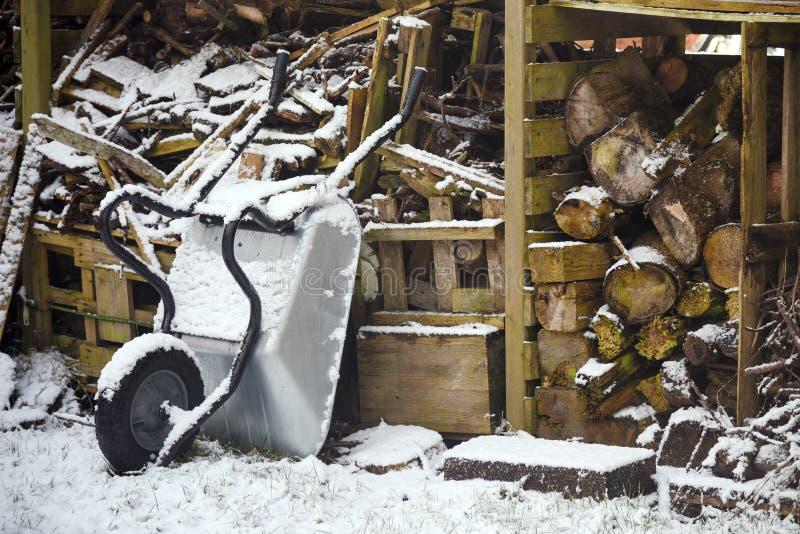 Brennholzklotz und eine Schubkarre in einer alten hölzernen Halle im sno stockbilder