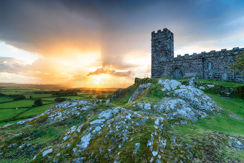Brentor on Dartmoor National Park in Devon. Dramatic sunset over the church on the top of Brentor on Dartmoor National Park in Devon stock photos