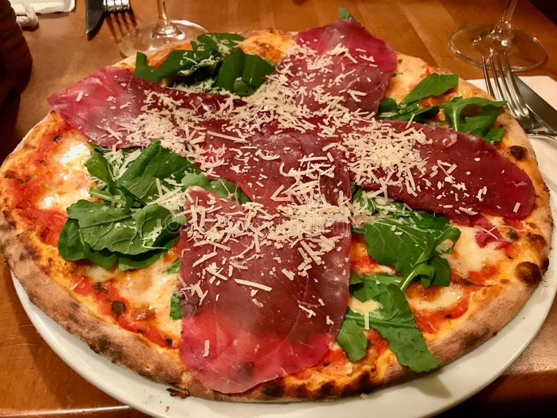 Bresaola比萨用帕尔马干酪、火箭队叶子或者芝麻菜/Rucola 免版税库存图片