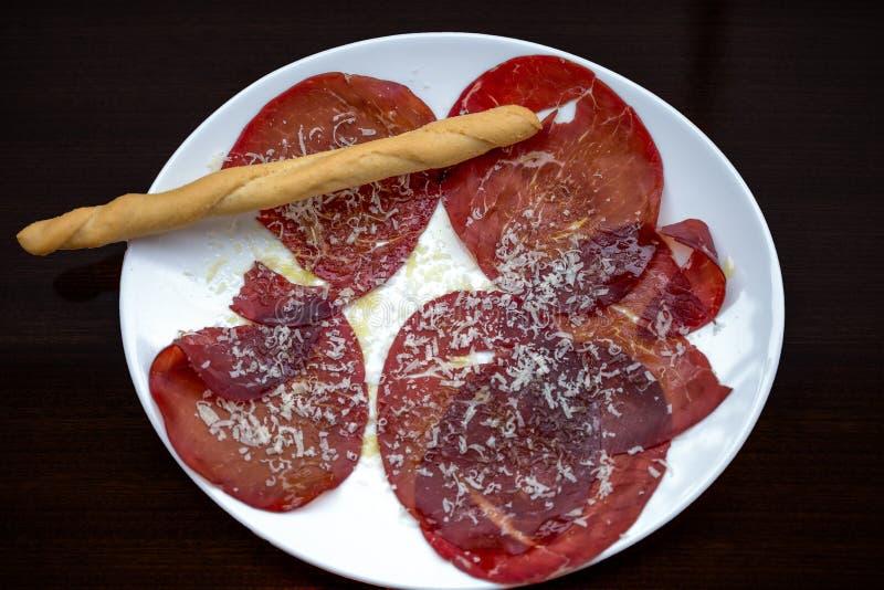 Bresaola,盐溶和风干治疗的未加工的牛肉意大利盘,典型地服务在与橄榄油选矿的切片, le 免版税库存照片