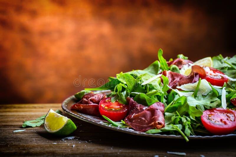 Bresaola высушенной говядины Томаты известка шпината младенца arugula bresaola салата и пармезан сыра стоковое фото rf