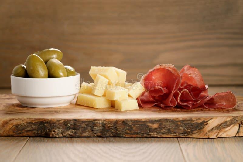 Bresaola con el queso parmesano y las aceitunas en tabla de cortar imagen de archivo libre de regalías