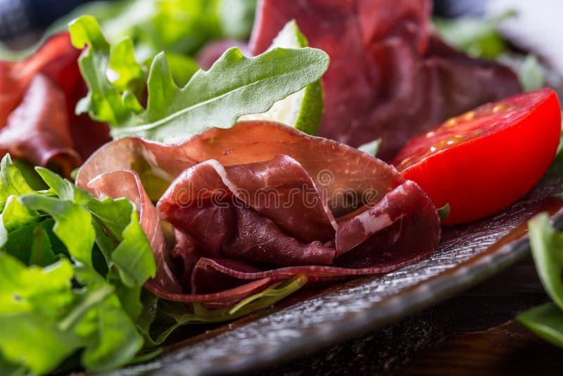 Bresaola de la carne de vaca secada Tomates cal de la espinaca del bebé del arugula del bresaola de la ensalada y parmesano del q imágenes de archivo libres de regalías