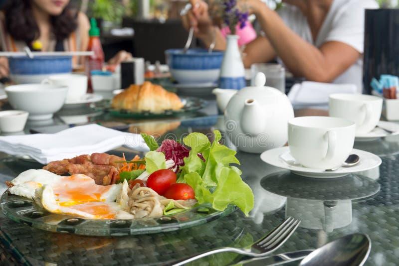 Breskfat uppsättning med stekt ägg och grönsaksallad med den tekrukan arkivfoto