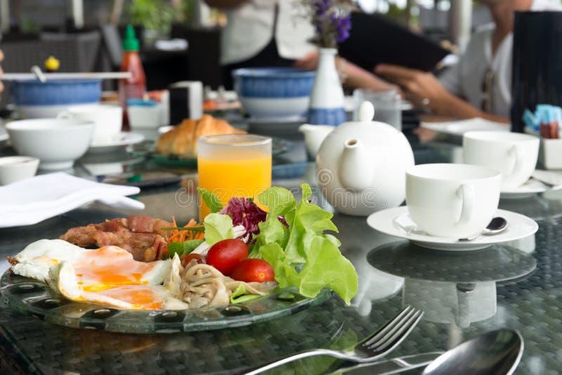 Breskfat uppsättning med stekt ägg och grönsaksallad med orange jui royaltyfri foto