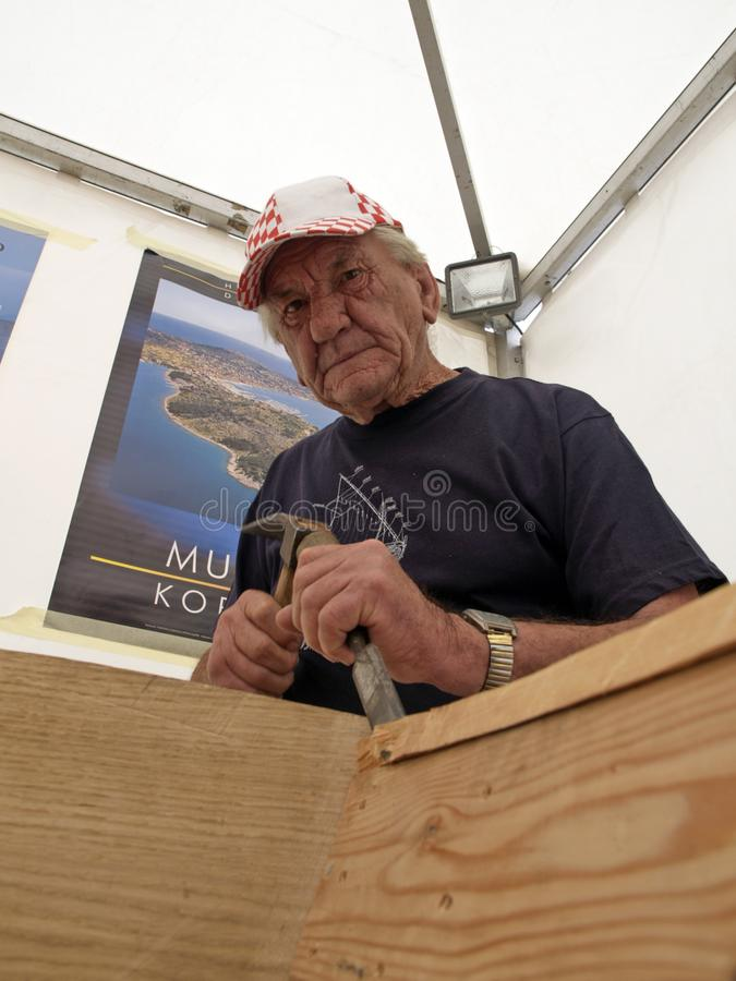 Carpenter works with a chisel on the restoration of an old wooden boat stock photos