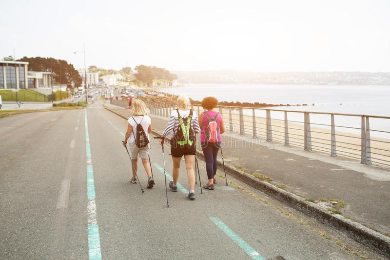 Brest, Francia 28 de mayo de 2018 tres mujeres felices que caminan junto en el camino cerca del océano en vacaciones de la aventu fotos de archivo libres de regalías
