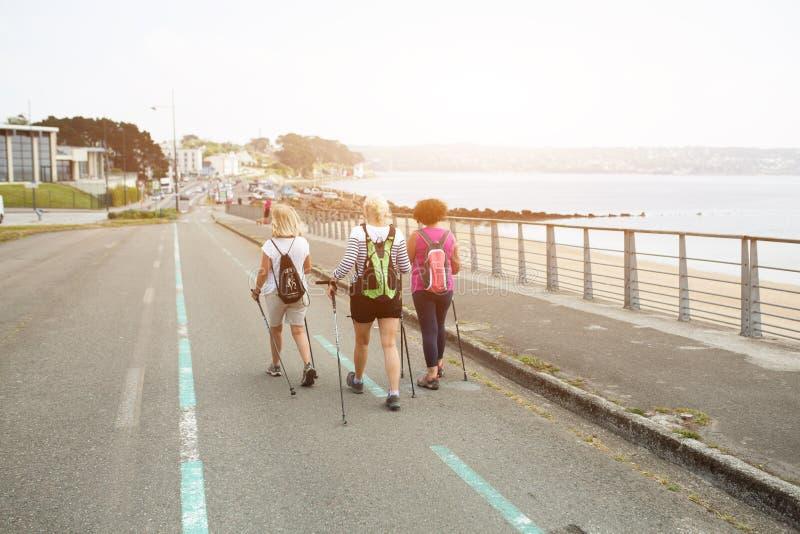 Brest, Francja 28 Maj 2018 trzy szczęśliwej kobiety wycieczkuje wpólnie na drodze blisko oceanu na przygoda wakacje opowiadać wpó zdjęcia royalty free