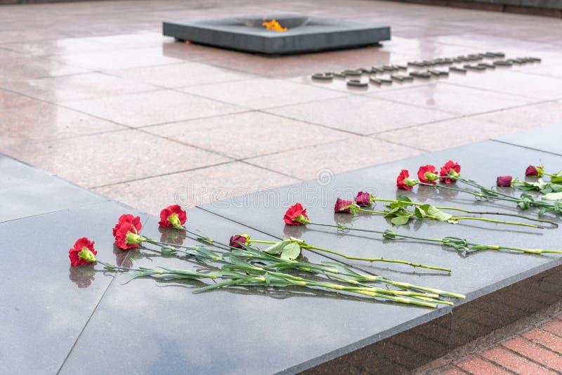 BREST VITRYSSLAND - JULI 28, 2018: Blommor på gravstenen av den okända soldaten och evigt ljus Titeln säger `-härlighet till hjäl royaltyfria foton