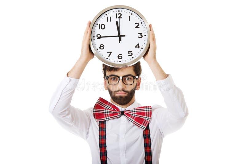 Bretelles de port d'homme tenant la grande horloge photographie stock libre de droits