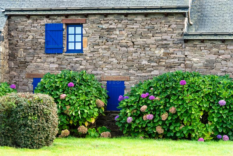 Breton house made of stones. Detail of an old typical breton house made of uneven stones. The windows are small and the shutters are painted in dark blue stock photos