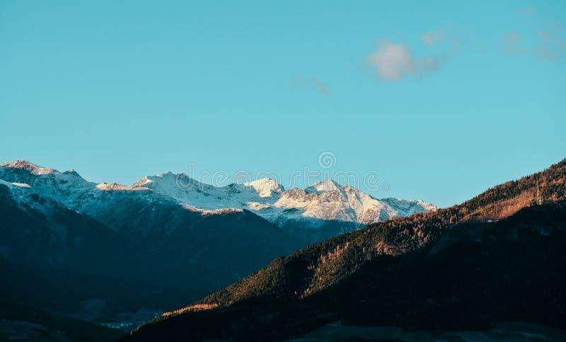 Brett skott av forested kullar och snöig bergfjällängar i avståndet på en solig dag arkivbild