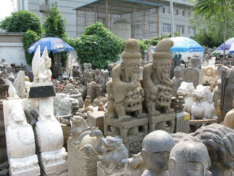 Brett statyfoto av män som sitter på kinesiska förmyndarelejon - Panjiayuan marknad arkivbild