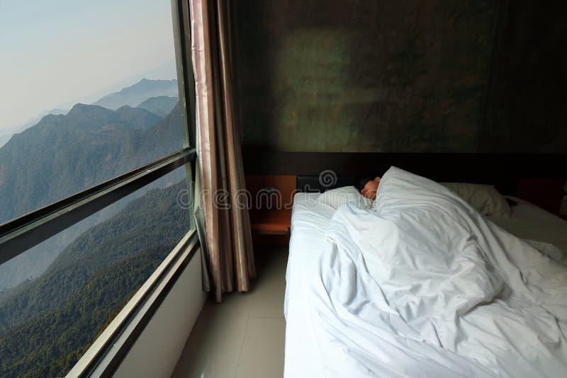 Brett vinkelskott av den stiliga unga mannen som bekvämt sover i sängen med härlig sikt för bergnaturmorgon från fönster royaltyfri bild