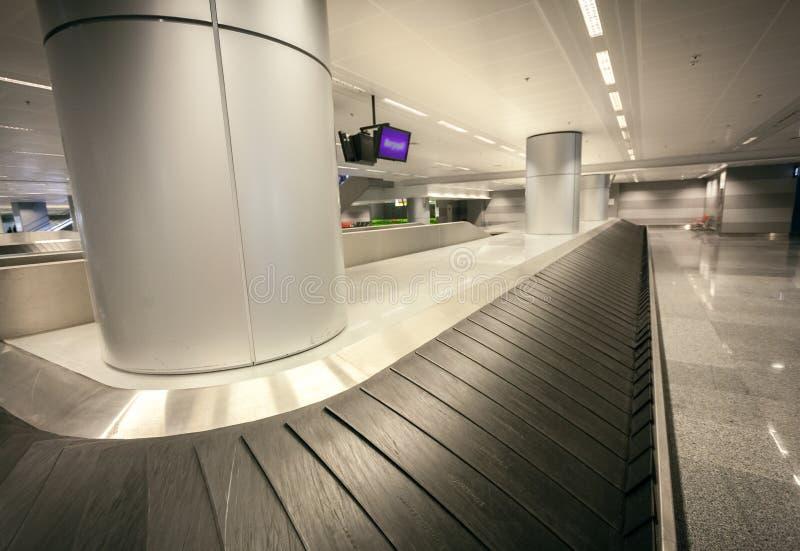 Brett vinkelskott av den tomma bagagereklamationen på flygplatsterminalen arkivbild