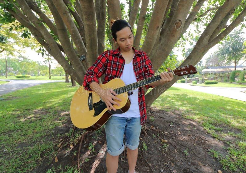Brett vinkelskott av ståenden av den stiliga unga mannen som spelar den akustiska gitarren i parkera utomhus med en stor trädbakg arkivfoton