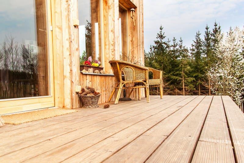 Bretterboden, hölzerne Terrasse an einem ökologischen Haus Geflochtene Stühle auf einer hölzernen Terrasse durch den Wald stockfotos