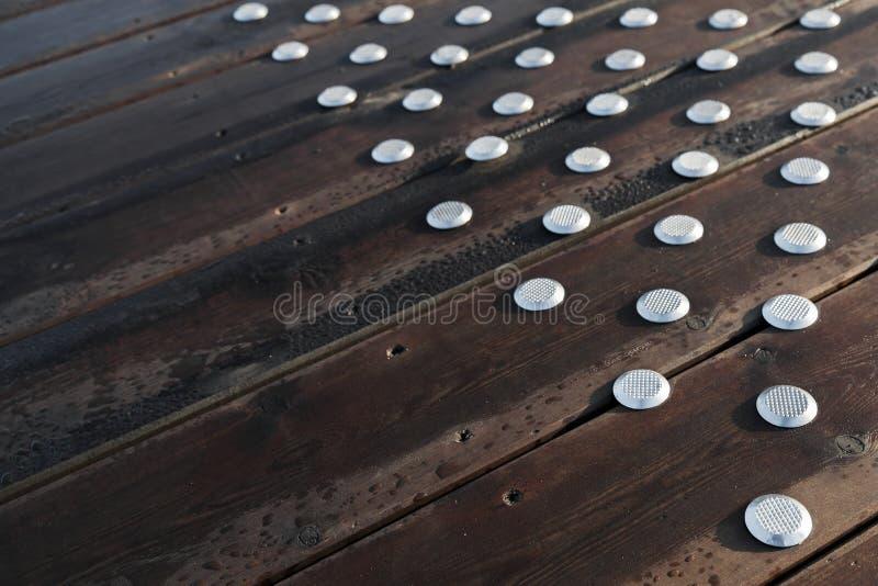 Bretterboden im Freien mit Stahlgleitschutzknöpfen lizenzfreies stockbild