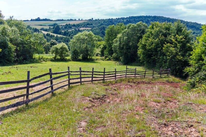 Bretterzaun auf einem Hügel mit einem unscharfen Schotterweg, der unten zur Unterseite absteigt lizenzfreies stockfoto