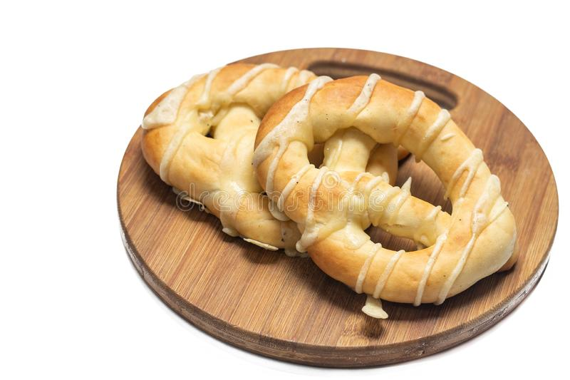Bretzels frais de boulangerie d'isolement au-dessus du fond blanc sur le conseil en bois photos libres de droits