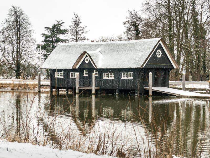 Breukelen, Nederland - 2010-02-14: Botenhuis in de sneeuw door Rivier Vecht stock foto
