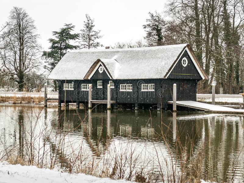 Breukelen, Netherlands - 2010-02-14: Boathouse in the snow by River Vecht. Breukelen, Netherlands - 2010-02-14: Wooden boathouse with thatched roof covered with stock photo