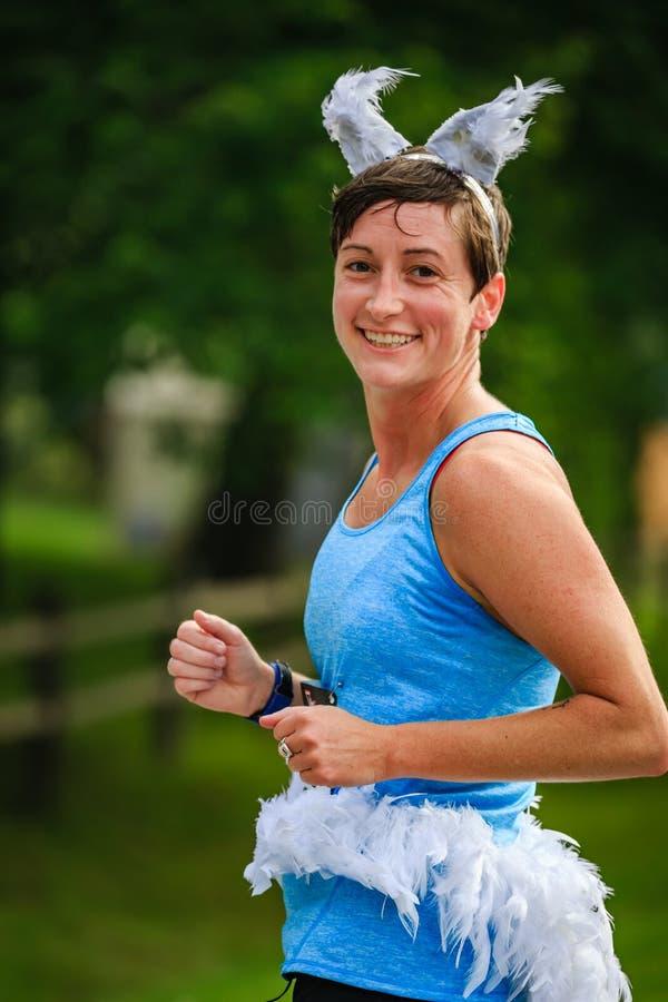 BREVARD NC-MAY 28, 2016 - kvinnlig löpare i en vit ekorredräkt i det vita ekorreloppet med över 350 löpare i Brevard royaltyfri bild