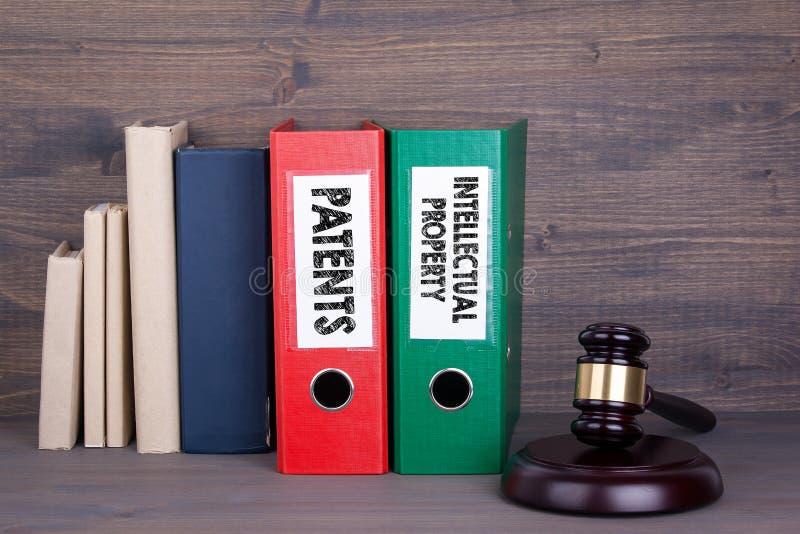 Brevetti e proprietà intellettuale Martelletto e libri di legno nel fondo Concetto della giustizia e di legge fotografia stock