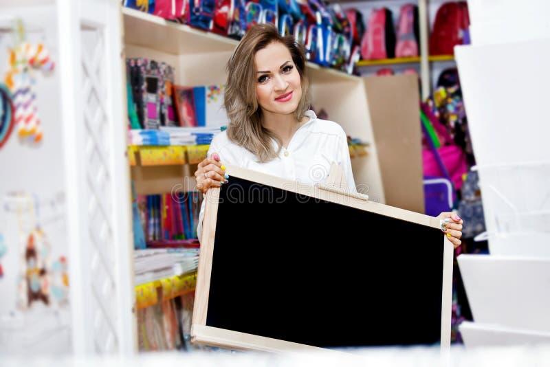 Brevpapper för supermarket för shopping för troley för ung kvinna för galleria för påse för skola för köp för bräde för moderträf fotografering för bildbyråer