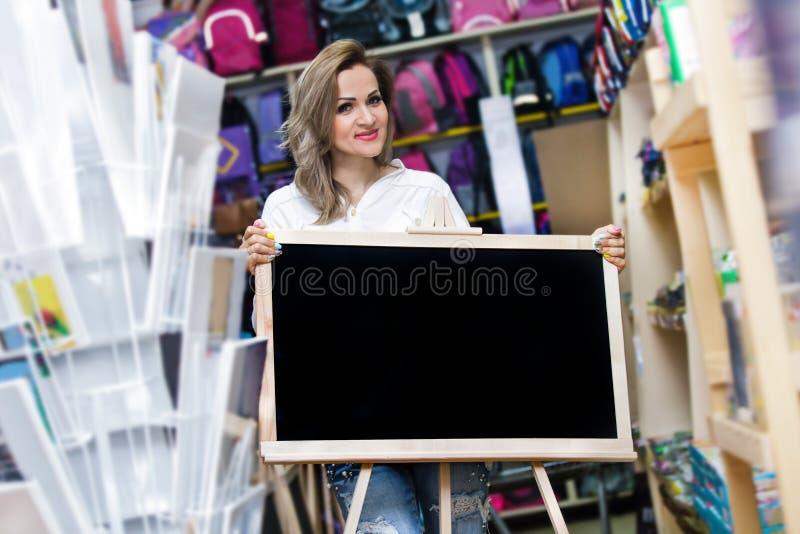 Brevpapper för supermarket för shopping för troley för ung kvinna för galleria för påse för skola för köp för bräde för moderträf arkivbild