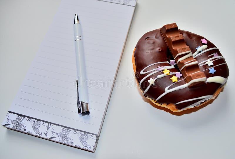 Brevpapper- och chokladdonuts för tom sida arkivfoto
