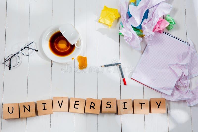 Brevpapper och ord UNIVERSITET som göras av bokstäver på träbakgrund royaltyfri bild