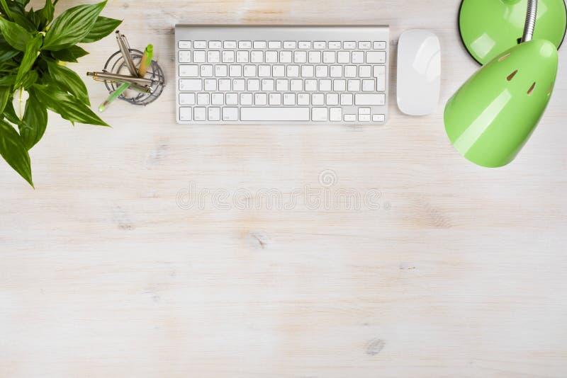 Brevpappersapplies, lampa, datortangentbord och mus på kontorstabellen arkivbild