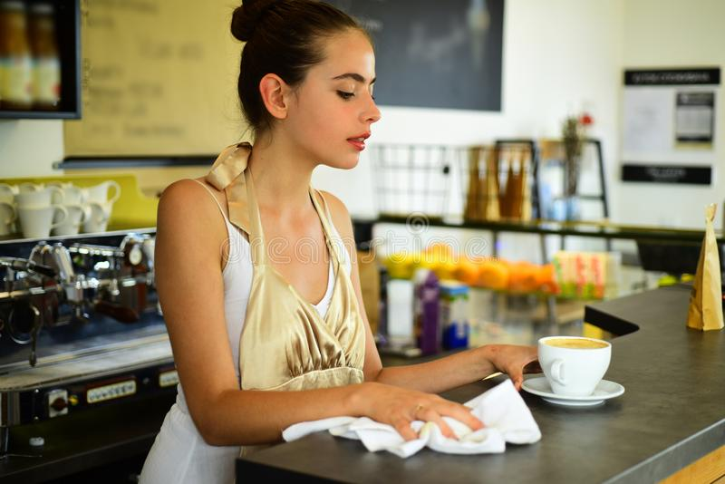 We brew your favorite beans. Barista serve cup of hot coffee drink with smile. Woman barista in coffee shop. Brewing. Coffee in coffeehouse. Pretty woman stand stock image