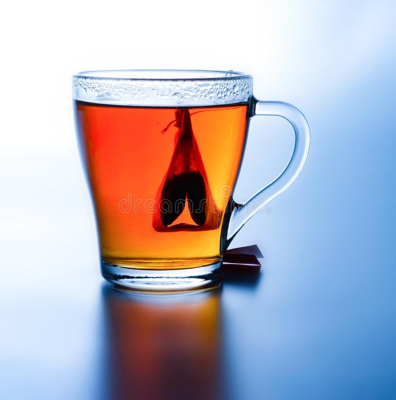 Brewed tea with a bag in a cup. High contrast. Saturated colors. White-blue background. Deep shadow. Close-up stock photo