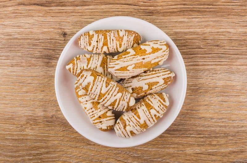 Brewed vitrificou cookies nos pires brancos na tabela de madeira imagem de stock royalty free