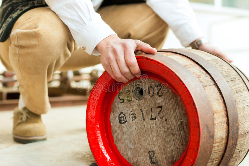 Brewer with beer barrel in brewery. A brewer in his brewery is loading a beer barrel stock photos