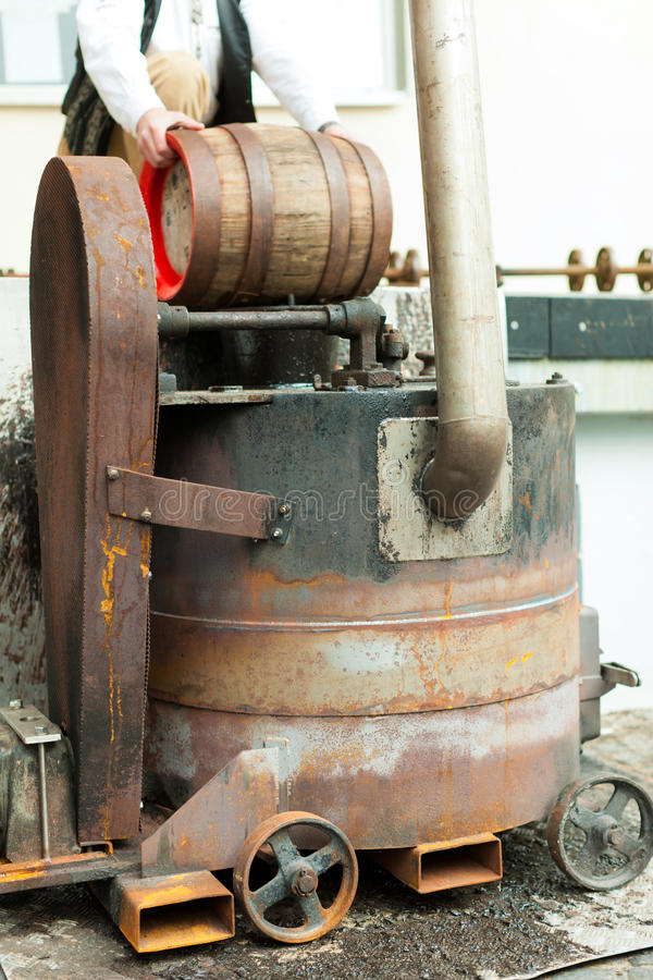 Brewer with beer barrel in brewery. Brewer in his brewery is traditionally sealing a beer barrel with tar pitch royalty free stock photography