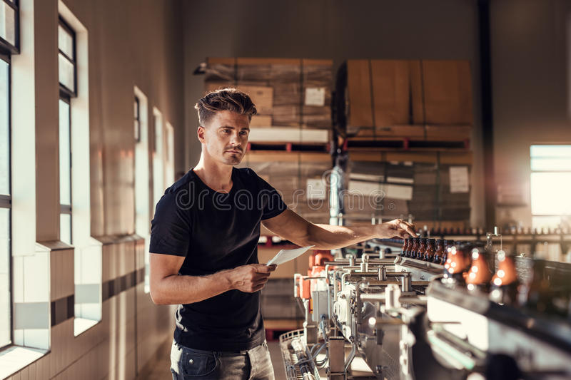 Brewer examining the beer production in brewery plant. Young man standing at the beer bottling machine in factory royalty free stock photography