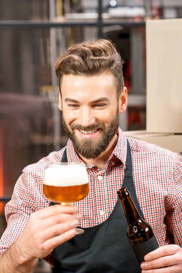 Brewer expertising beer. Handsome brewer expertising beer in the glass at the manufacturing royalty free stock image