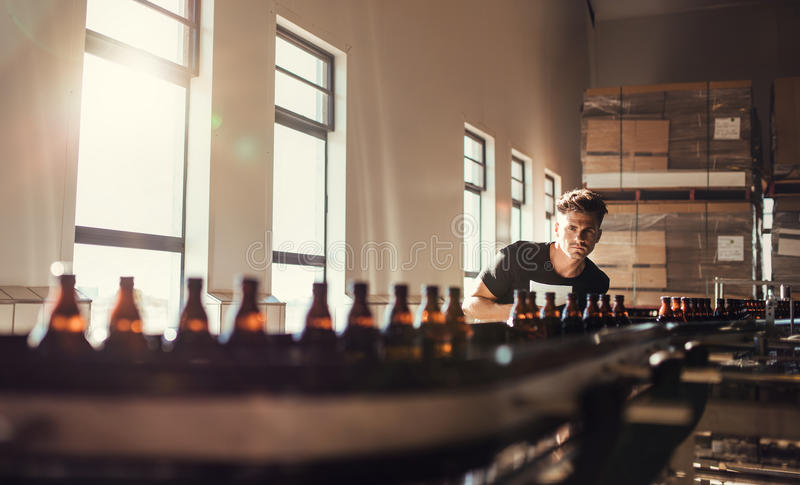 Brewer looking at conveyor with beer bottles. Young man supervising the manufacturing process of beer at brewery factory royalty free stock photography