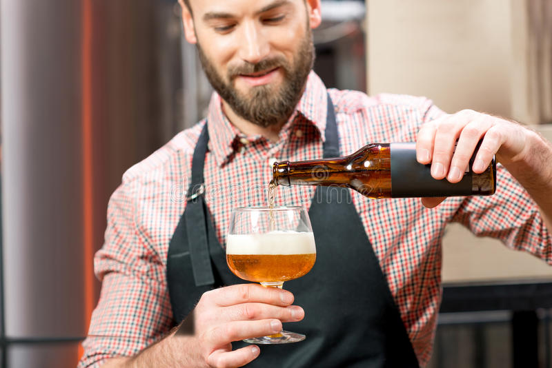 Brewer pouring beer. Handsome brewer in apron and shirt pouring beer into the glass at the manufacturing. Image focused on the bottle and glass royalty free stock photo