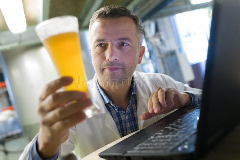 Brewer in uniform tasting beer. Man stock photos