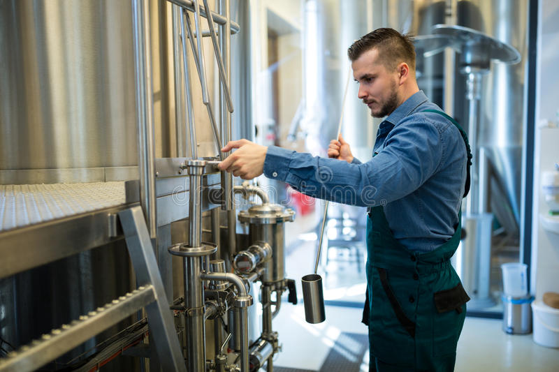 Brewer working at brewery. Attentive brewer working at brewery royalty free stock photos