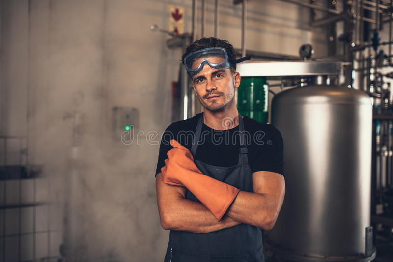 Brewer working in brewery plant. Portrait of young man in protective workwear standing in brewery factory. Brewer working in brewery plant with industrial royalty free stock image