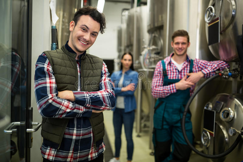 Brewers posing at brewery factory royalty free stock photo