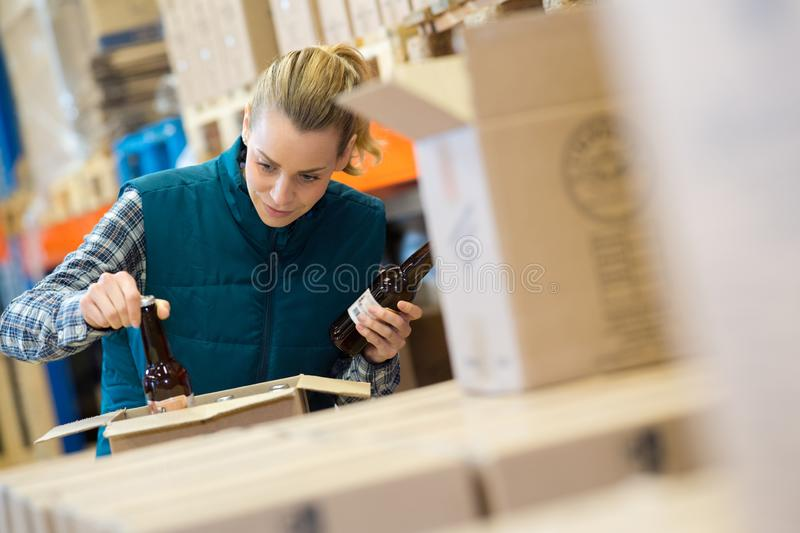 Brewery worker checking bottle beer in cardboard box royalty free stock images